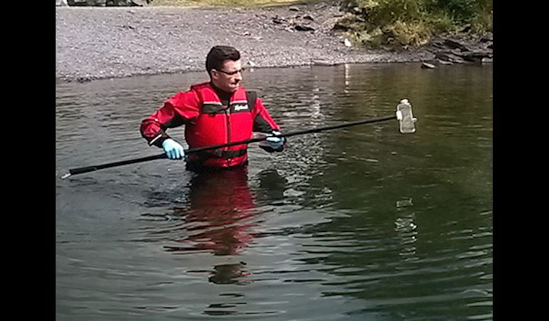Man testing the water quality at llyn padarn