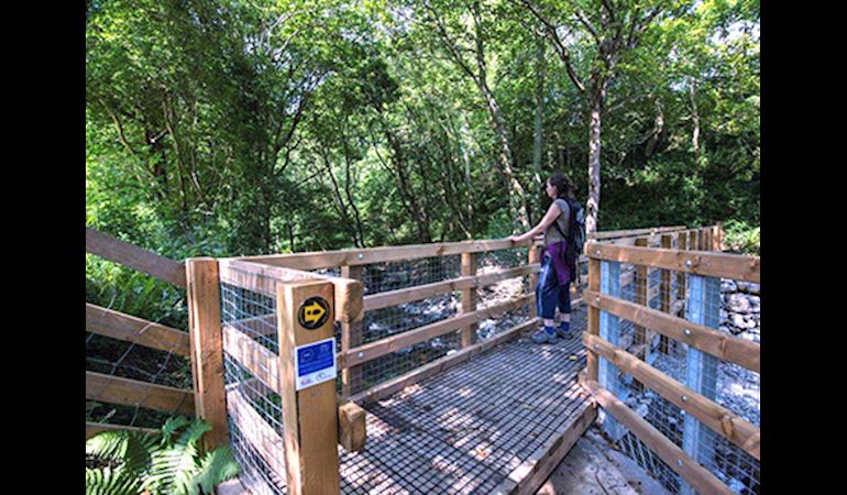 Woman using the improved path to cross a river