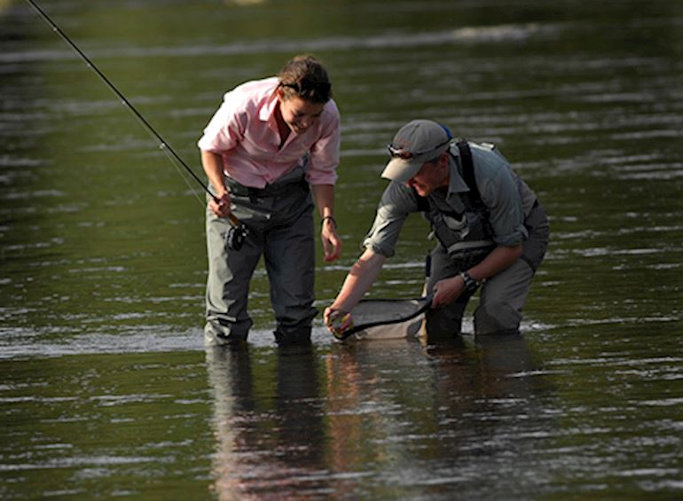 Two fishermen catching a fish in a river