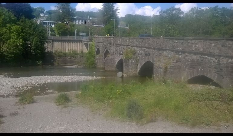 Low level river flowing under a bridge with multiple arches