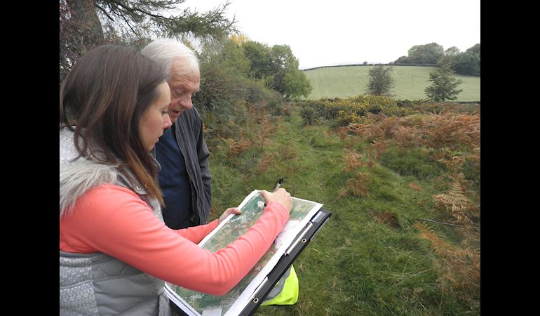 Two people marking on a map where to cut on the Halkyn Mountain