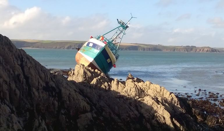 A small fishing boat stranded on some rocks