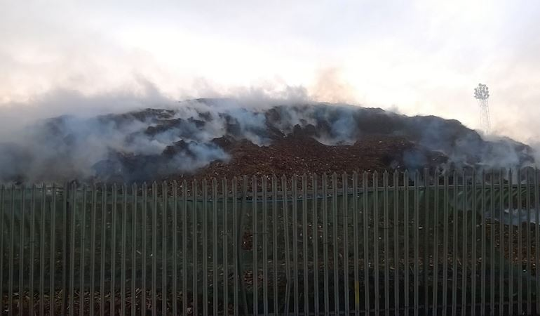 Smoke bellowing from a pile of wood chip surrounded by a metal fence