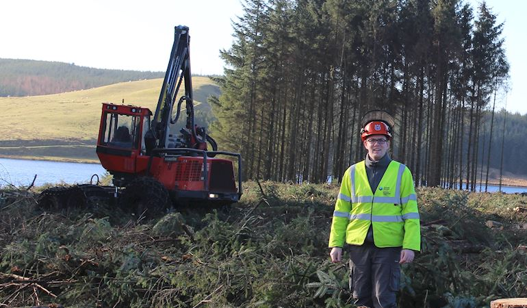 Man in a high visibility jacket stands in front of a digger and a small group of trees