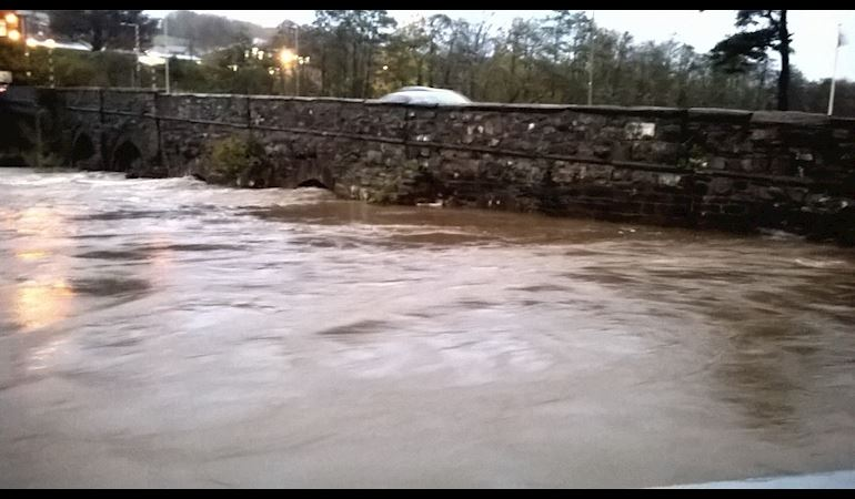Fast flowing high river against an old brick bridge