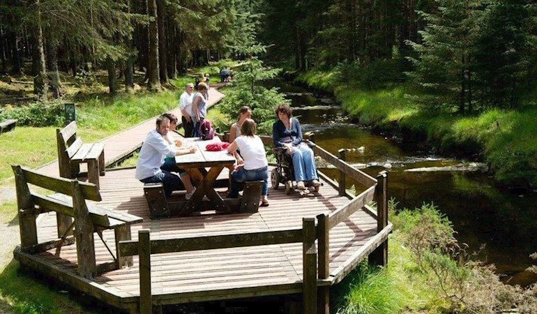 People gathered around a picnic bench next to a river.