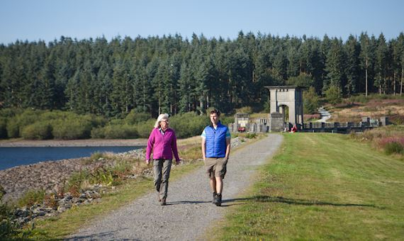 Man and woman walk across the Alwen dam