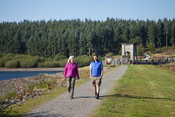 Man and woman walk across the Alwen dam