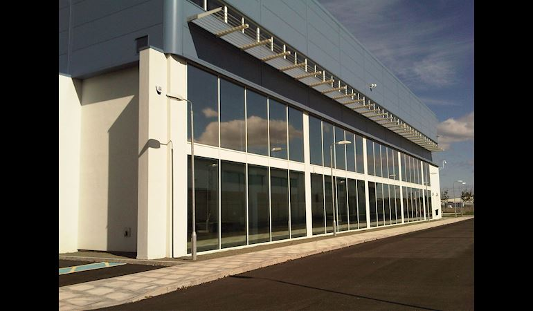 Long building with floor to ceiling glass windows and a grey roof