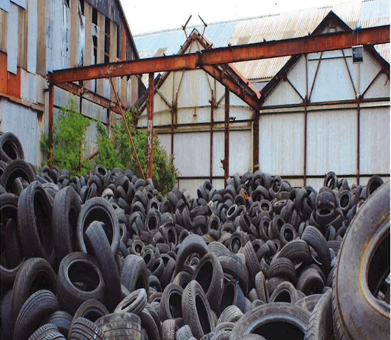Lots of car tyres piled up outside a warehouse
