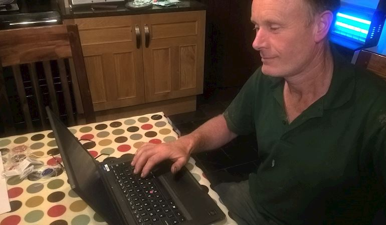 Man sitting at the kitchen table with laptop