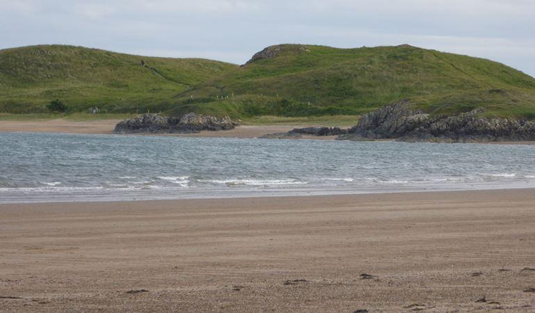 Photo showing the green landscape of Ynys Llanddwyn from Newborough beach