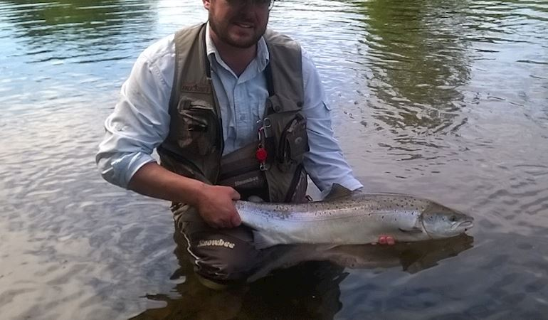Angler holding a salmon while standing in the River Usk