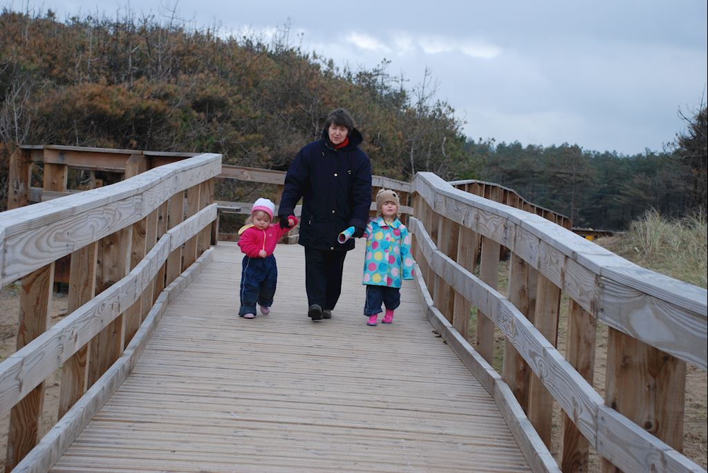 Woman walking along a bridge with two small children