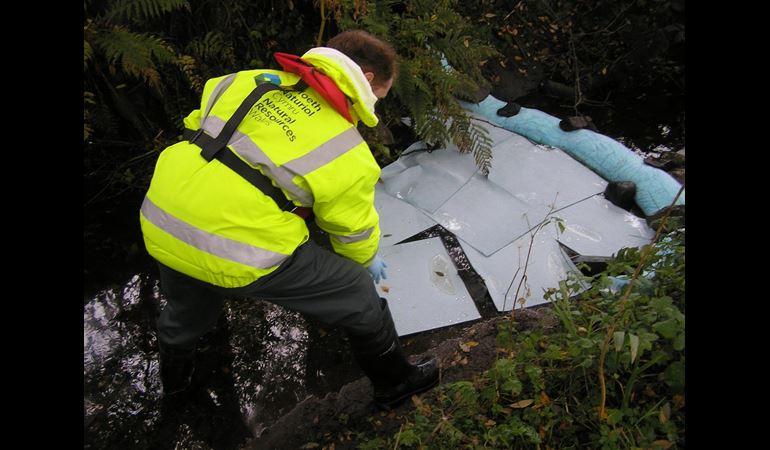 NRW staff member deploying an absorbent boom
