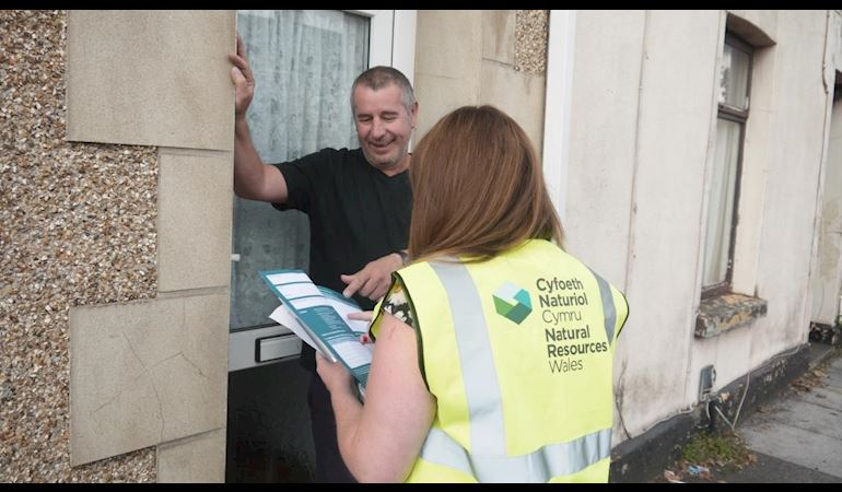 NRW staff member explaining a flood plan to a member of the public