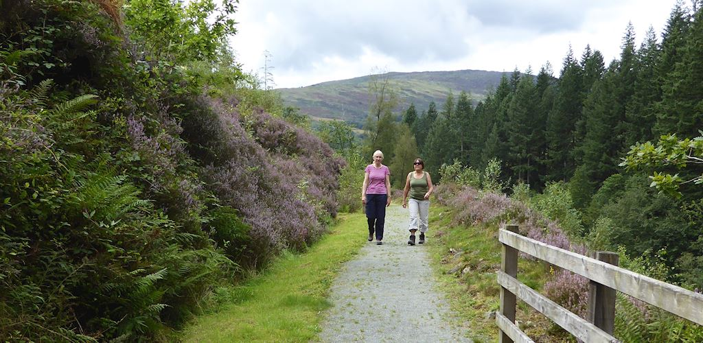 Two women walking along a trail at Pont Llam yr Ewig, Coed y Brenin Forest Park