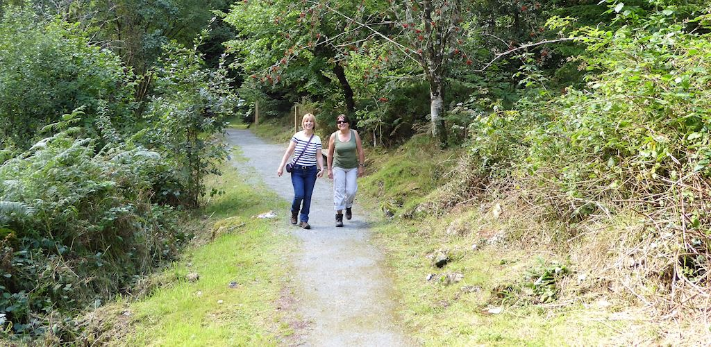 Two women walking along a trail in Pandy at Coed y Brenin Forest Park