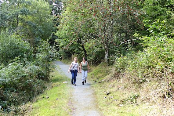 Two women walking along a trail in Pandy at Coed y Brenin Forest Park
