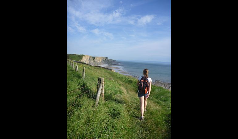 Woman walking along a coastal path