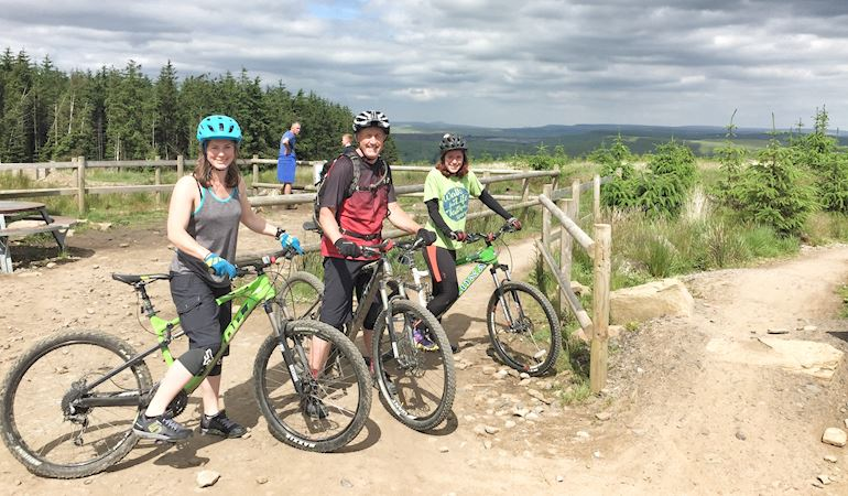 Three people on a bike trail standing with their bikes