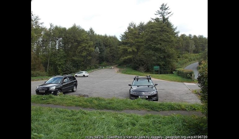 Photo of car park surrounded by trees with a road running along the right