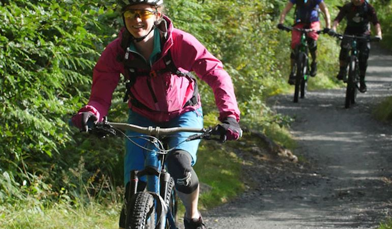 Image of a woman mountain biking with two cyclists in the background