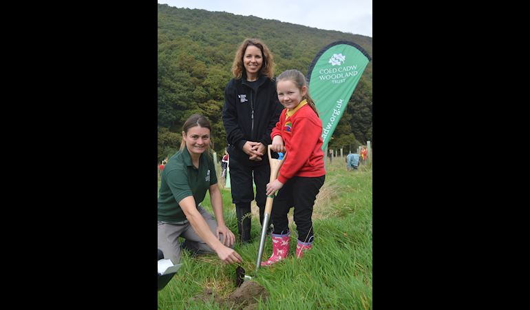 Rebecca Good (Woodland Trust), Kate Thomson (NRW) and a school girl planting a tree