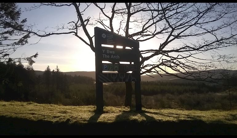 Y Bwa vistor centre sign with the sun setting in the background behind a silhouette of a tree