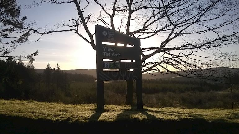 The arch visitor centre sign with the sun setting in the background behind a silhouette of a tree