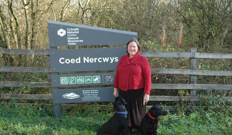 Clare Pillman CEO, wearing red jacket stood in front of the NRW Coed Nercwys sign with two black labrador dogs