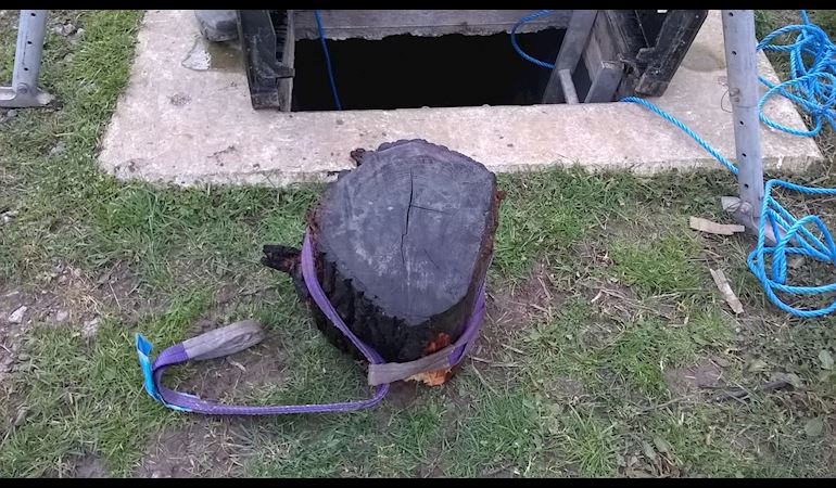 A large log on the ground next to the opening to the tidal flap with a lifting strap attached