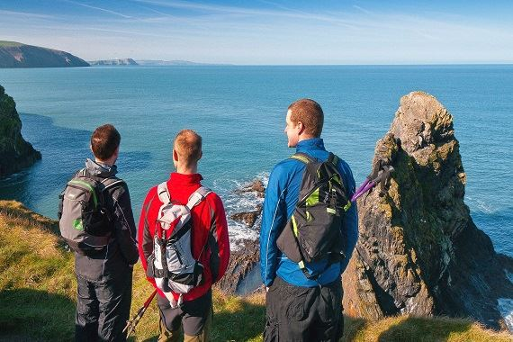 Three people looking out at the sea - Credit Visit Wales