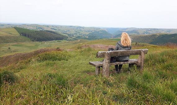 Woman on bench looking out over hills