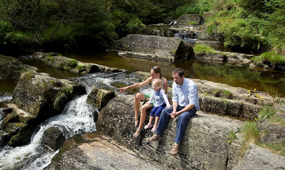 Family sitting on rocks near a river