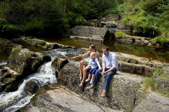 Family sitting on rocks near a river