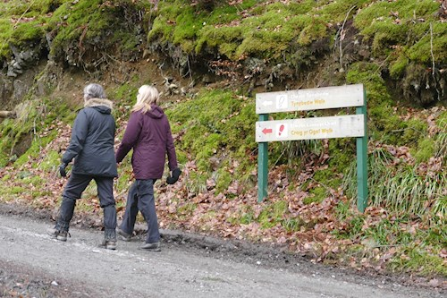 Two women walking past sign