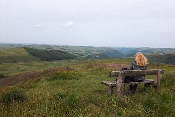 Woman on bench looking over countryside