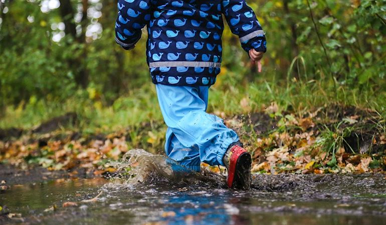Child walking through puddles