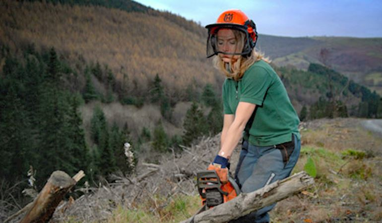 Photo of Caroline Riches with a saw