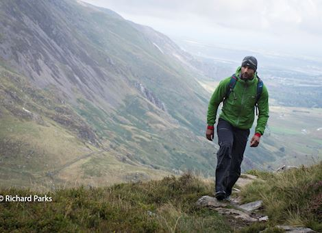 Photo of Richard Parks walking up a mountain with a view down the mountain in the background