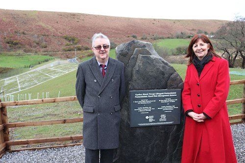 Photo of the First Minister and Minster for Environment standing next to an engraved slate plaque on a large piece of stone from a local quarry, with the flood embankment and Dulais valley behind them.