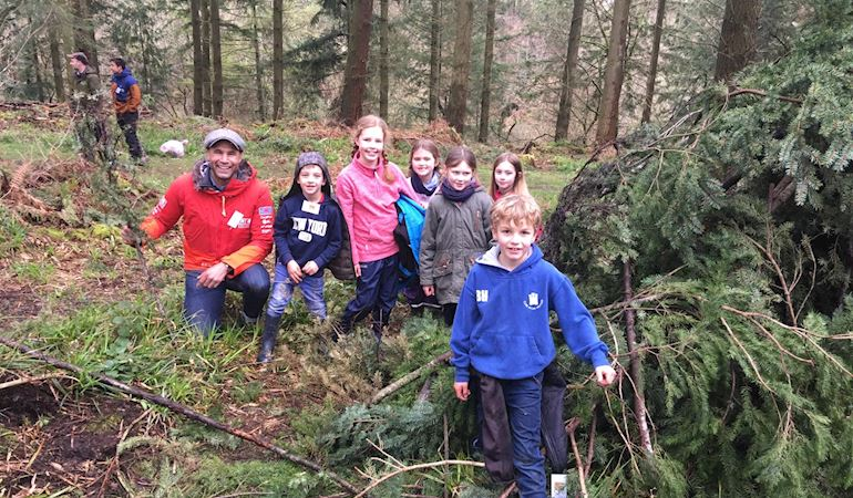 Photo of children in a woodland learning about the outdoors with Welsh adventurer Richard Parks