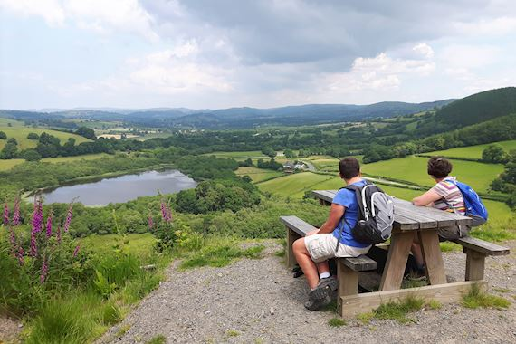 Two people on bench looking at the view