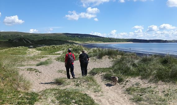Two men walking along dune grasslands