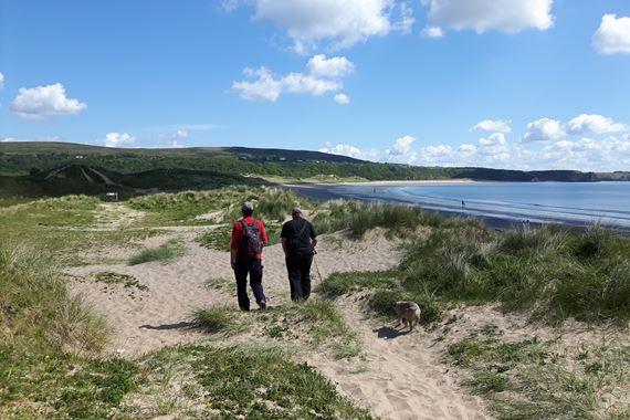 Two men walking along dune grasslands