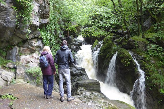 Man and woman by waterfall