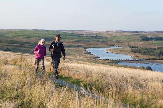 Man and woman walking near reservoir