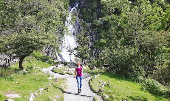 Woman walking near Coedydd Aber waterfall