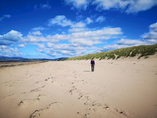 Woman walking on the beach next to dunes